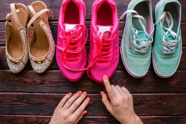 Dziewczyna wybiera buty na drewnianym tle