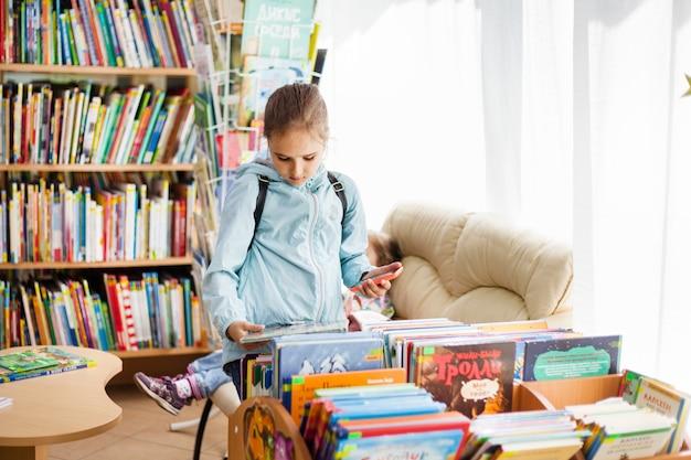 Dziewczyna wybiera książki w bibliotece, różne książki do czytania dla dzieci w wieku szkolnym i przedszkolaków, edukację, wiedzę, zrozumienie, bajkę, historię