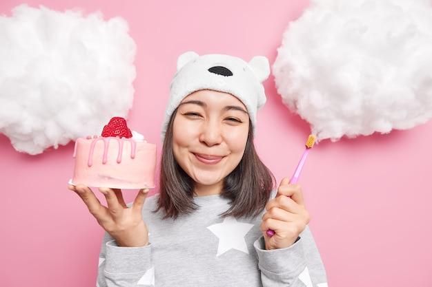 Dziewczyna wybiera między słodkim, smacznym ciastem a zdrowiem, trzymając w zębach szczoteczkę do zębów, opowiada o paskudnym jedzeniu, ubrana w strój do spania
