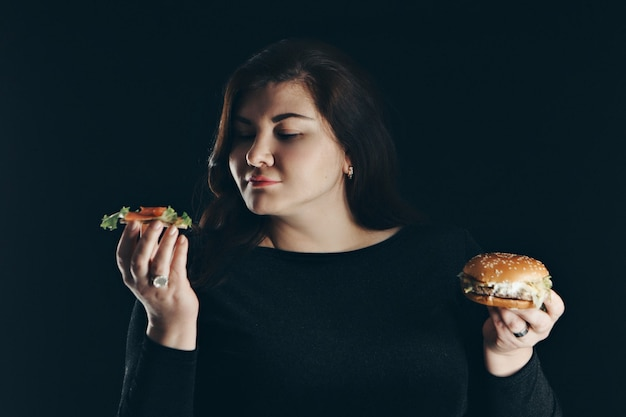 Dziewczyna wybiera między zdrowym a pysznym jedzeniem. kanapka z rybą i burger w rękach kobiety. pojedynczo na czarnym tle. skopiuj miejsce