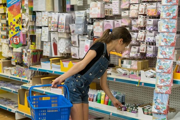 Dziewczyna wybiera przybory szkolne w sklepie. kupowanie przyborów szkolnych w angielskim sklepie.