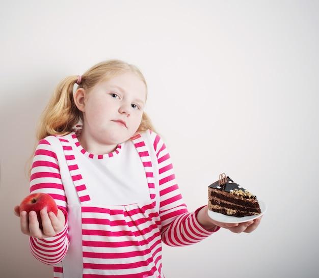 Dziewczyna wybiera słodkie ciasto i czerwone jabłko