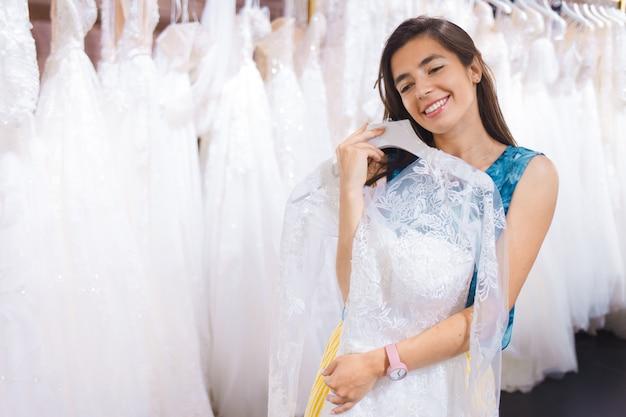 Dziewczyna wybiera suknię ślubną.