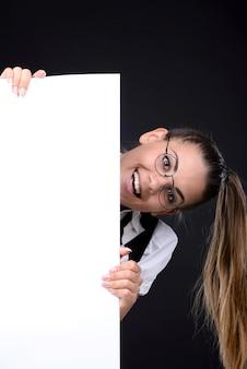 Dziewczyna wychodzi zza pustej plakietki i uśmiecha się.