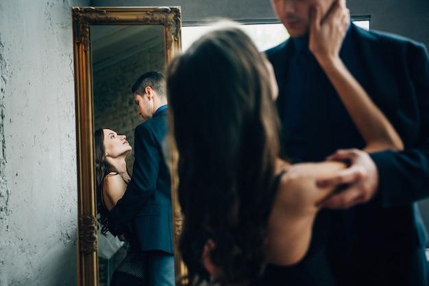 Dziewczyna wyciąga rękę do faceta, a ich obrazy odbijają się w lustrze w podłodze
