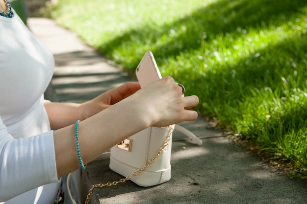 Dziewczyna wyciąga telefon z torby na ulicy