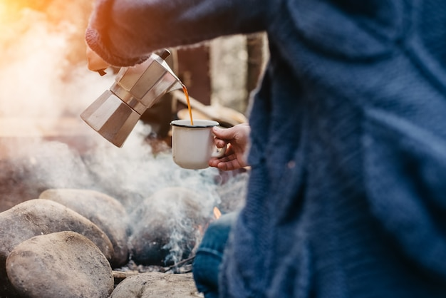 Dziewczyna wycieczkowicz nalewa sobie gorącą kawę w pobliżu ogniska w czasie zachodu słońca.