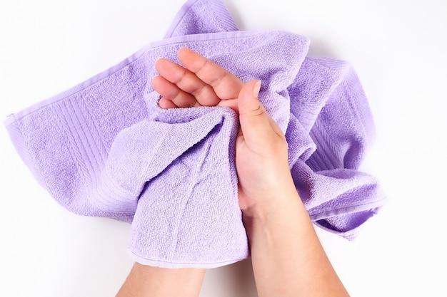 Dziewczyna wyciera ręce fioletowy ręcznik na białym tle. widok z góry.