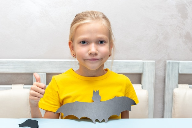 Dziewczyna wycina w domu nietoperza halloween własnymi rękami z czarnego papieru rzemieślniczego nożyczkami. dziewczyna pokazuje wyciętego z papieru nietoperza. koncepcja domu halloween wakacje.