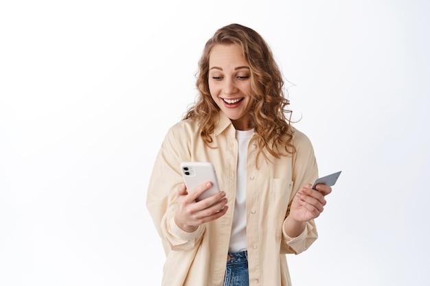 Dziewczyna wygląda na szczęśliwą na ekranie smartfona i uśmiecha się, trzyma plastikową kartę kredytową, składa zamówienie, stoi nad białą ścianą