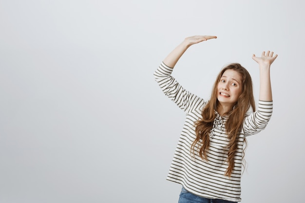 Dziewczyna wygląda niewygodnie, gdy trzyma coś dużego