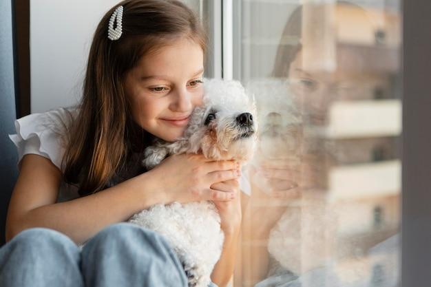 Dziewczyna wygląda przez okno z psem
