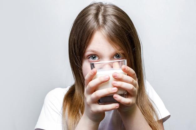 Dziewczyna wygląda złośliwie zza szklanki mleka