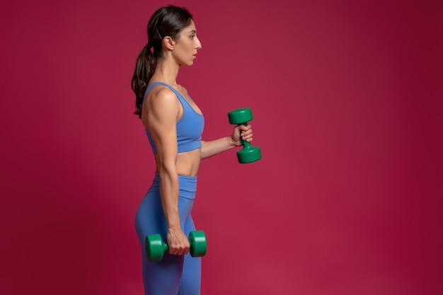 Dziewczyna wykonująca trening górnej części ciała z hantlami na bordowej ścianie