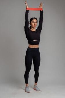 Dziewczyna wykonująca trening górnej części ciała z opaską oporową na szarej powierzchni