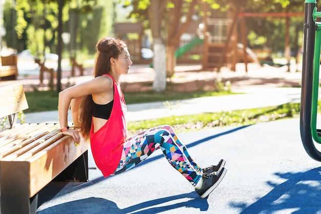 Dziewczyna wykonuje pompki ćwiczeń z ławeczki na placu zabaw w słoneczny letni poranek