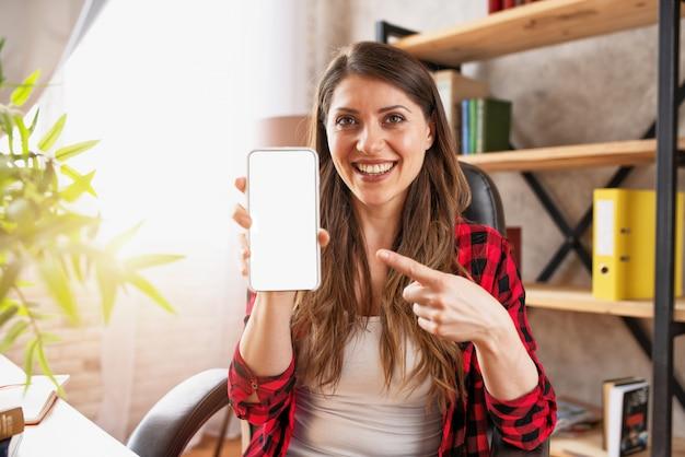 Dziewczyna wykonuje rozmowę wideo ze swoją rodziną z powodu koronawirusa covid19. białe znaki na smartfonie dla tekstu