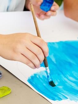 Dziewczyna wykonuje rysunek na papierze niebieską farbą. dziewczyna trzyma pędzel w ręku podczas rysowania