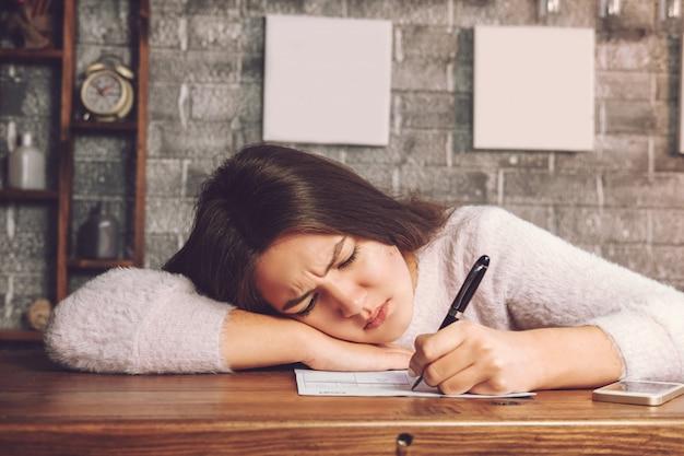 Dziewczyna wypełnia formularz, dziewczyna jest zmęczona i zdenerwowana