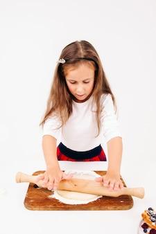 Dziewczyna wyrabiania ciasta z wałkiem do ciasta