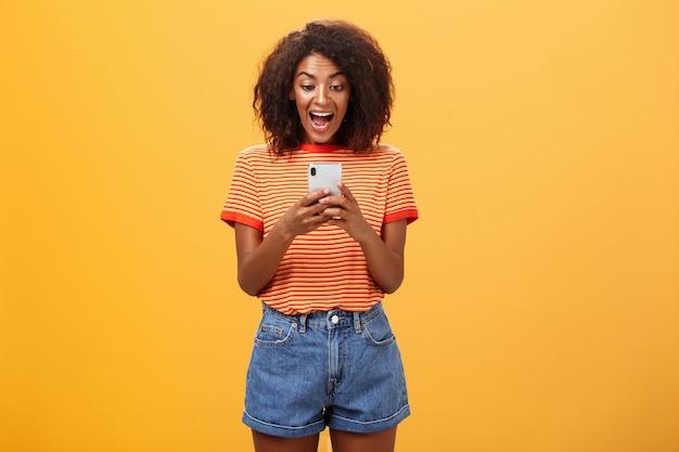 Dziewczyna wyrażająca podekscytowanie i radość patrząc na smartfona.