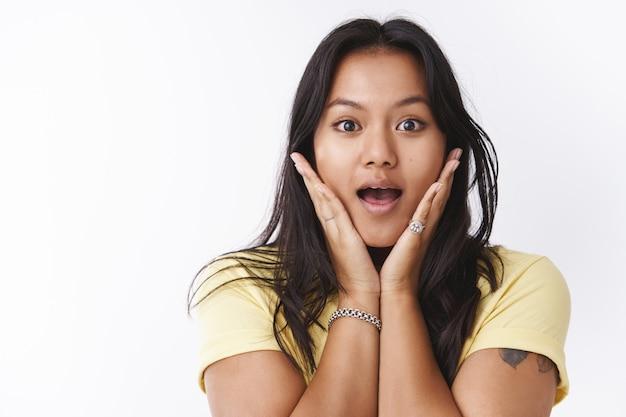 Dziewczyna wyrażająca zaskoczenie i zdumienie, gdy słyszy niewiarygodnie dobre wieści reagując na niesamowite plotki, zachwycona i rozbawiona, dysząc, opadająca szczęka ze zdumienia i trzymająca dłonie na twarzy