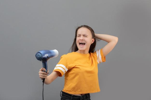 Dziewczyna wysuszyć włosy na białym tle na szarej ścianie