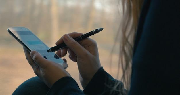 Dziewczyna wysyłająca sms-y na smartfonie w pociągu