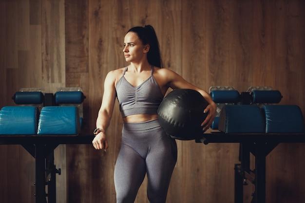 Dziewczyna z atletycznej budowy ciała z fitball na tle drewnianej ściany siłowni do crossfitu
