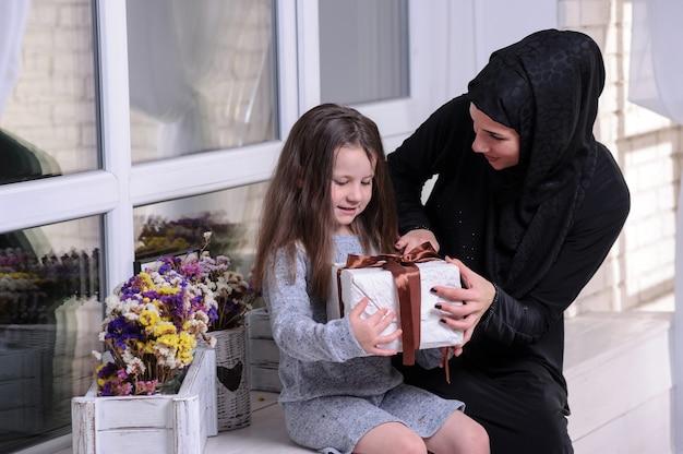 Dziewczyna z azji południowo-wschodniej z pudełkiem. styl życia rodziny muzułmańskiej. szczęśliwy uśmiechający się malajski rodzice i dziecko.