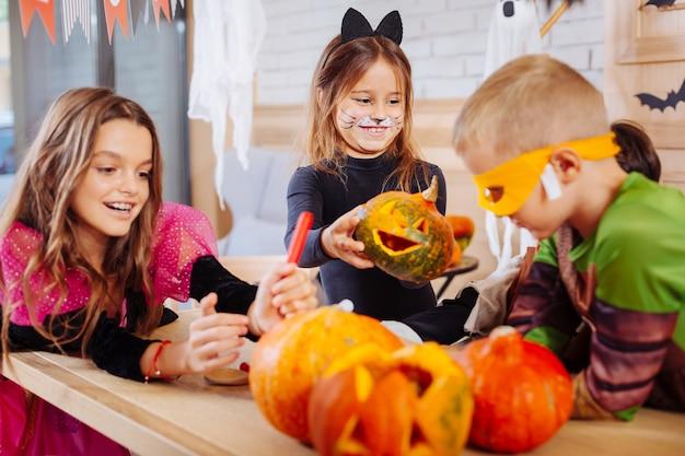 Dziewczyna z banią. śliczna uśmiechnięta dziewczyna ubrana w kostium kota czuje się podekscytowana, trzymając małą rzeźbioną dyni halloween