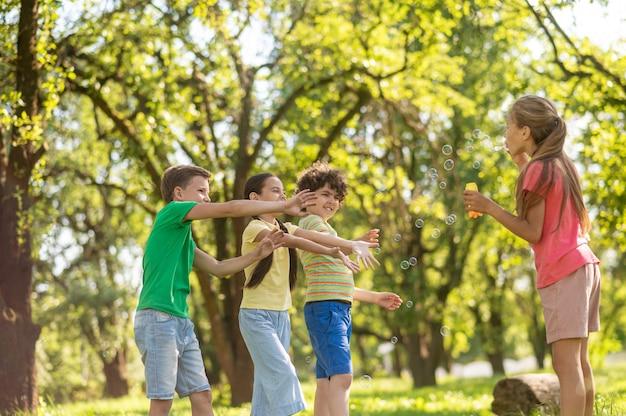 Dziewczyna z bańkami mydlanymi i przyjaciółmi machającymi rękami