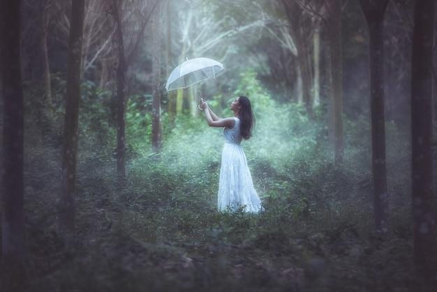 Dziewczyna z białym parasolem stoi w lesie.