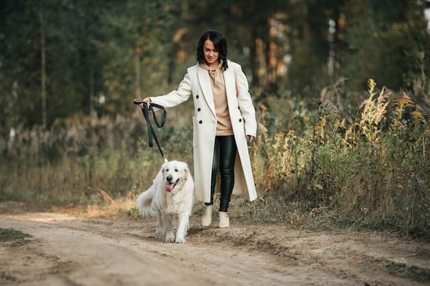 Dziewczyna z białym psem golden retriever na leśnej ścieżce