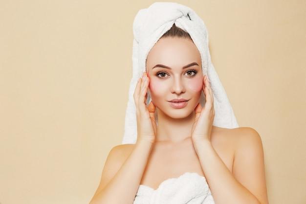 Dziewczyna z białym ręcznikiem na głowie na beżowym tle