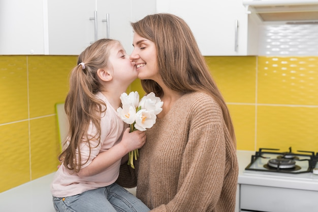 Dziewczyna z białymi tulipanami całuje matkę na policzku