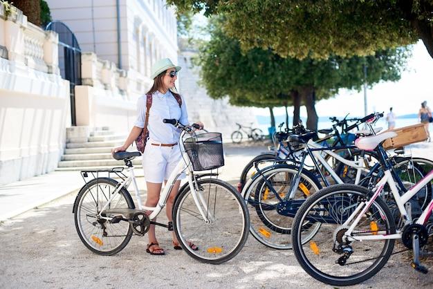 Dziewczyna z bicyklem w cieniu drzewek palmowych przy roweru parking na jaskrawym słonecznym dniu