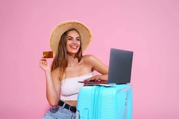 Dziewczyna z biletami na laptopa, karta kredytowa i paszport, będą podróżować siedząc obok walizki w skrócie...