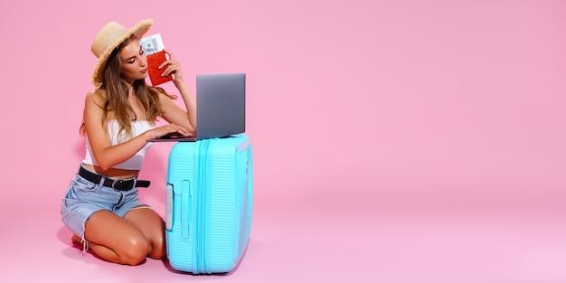 Dziewczyna z biletami na laptopa, pieniędzmi i paszportem jedzie w podróż siedząc obok walizki w krótkich spodenkach...
