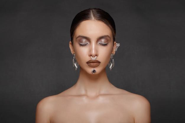 Dziewczyna z biżuterią na szarym tle, oczy zamknięte. portret piękna twarzy. makijaż, fryzura.