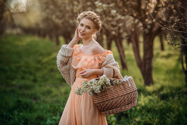 Dziewczyna z blond włosami w lekkiej sukience w kwitnącym ogrodzie. dziewczyna w pięknej sukience i swetrze z dzianiny cieszy się zachodem słońca w ogrodzie kwitnienia gruszy, z koszem kwiatów