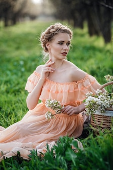 Dziewczyna z blond włosami w lekkiej sukience w kwitnącym ogrodzie. koncepcja kobiecej mody wiosennej.