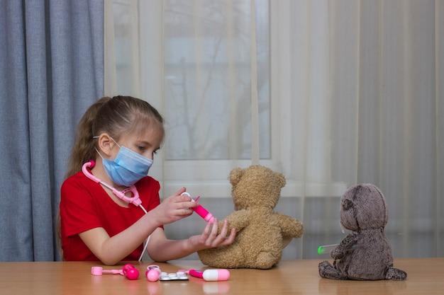 Dziewczyna z blond włosami w wieku przedszkolnym maska medyczna bawi się w szpitalu zabawkami robi szczepienia