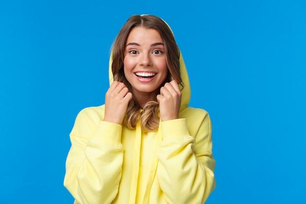 Dziewczyna z blond włosami w żółtej bluzie z kapturem
