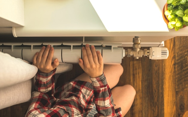 Dziewczyna z bosymi stopami obok grzejnika grzejnikowego w tle nowoczesnego wnętrza domu