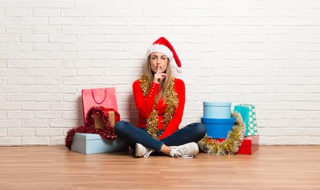 Dziewczyna z boże narodzenie kapeluszem i wiele prezentami świętuje boże narodzenie wakacje
