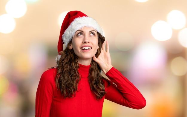 Dziewczyna z boże narodzenie kapeluszowym słuchaniem coś nad unfocused ścianą