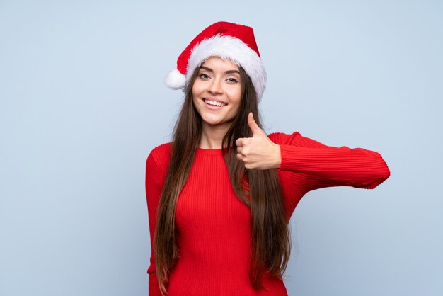 Dziewczyna z bożymi narodzeniami kapeluszowymi nad odosobnionym błękitem daje aprobata gestowi