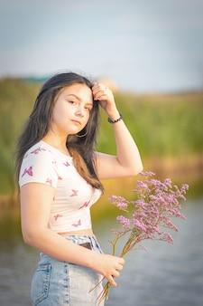 Dziewczyna z bukietem kwiatów w dłoni poprawia swoje długie ciemne włosy o zachodzie słońca nad jeziorem.