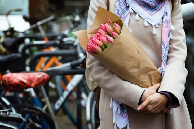 Dziewczyna z bukietem tulipanów stojąca na ulicy amsterdamu